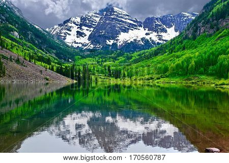 Mountain peak reflection in calm lake. Maroon Bells near Aspen Snowmass Colorado State USA.