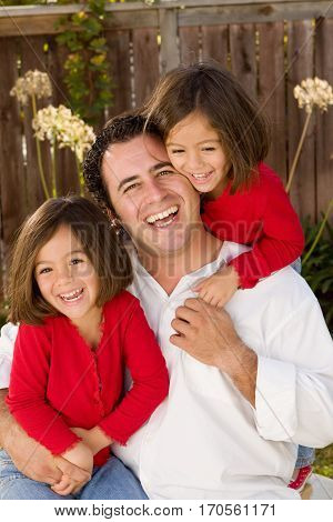 Portrait of a happy Hispanic father hugging his daughters.