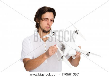 Young man holding a flying drone with the camera. Isolated on white.
