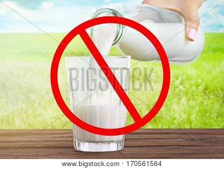 Allergic food products concept. Woman pouring milk from bottle into glass and restriction sign on nature background