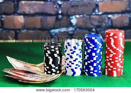 Casino chips and money on green poker table. Color poker chips in column form on brick wall background. Games of chance theme.