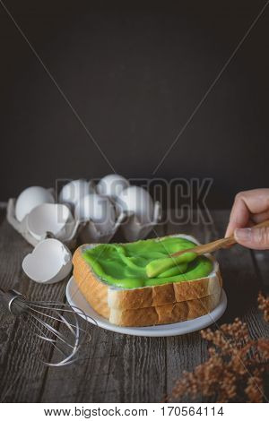 hand applying pandan custard cream on to toasted easy breakfast in morning with bread and custard cream topping