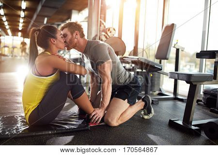 Fitness coach kiss girlfriend on training in gym