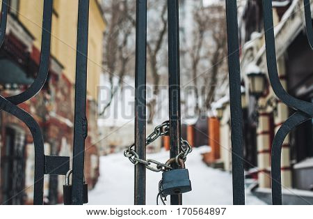 Lock and chain on gates and private residence on background