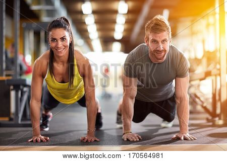 Couple doing exercise for hand muscles at fitness training