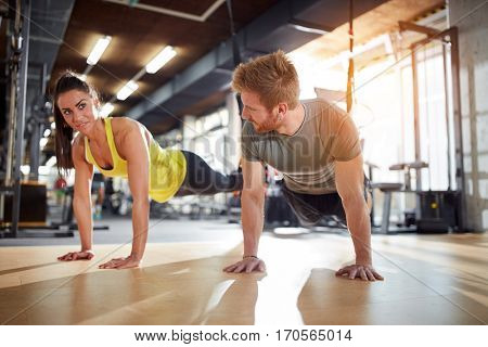Female and male doing exercises for strengthen hands muscles in gym