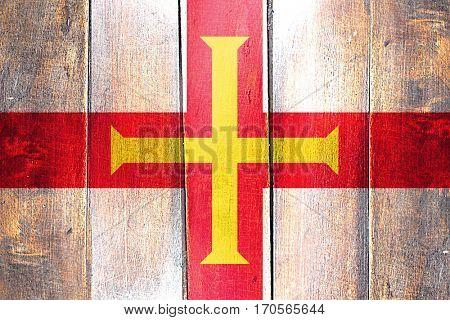 Vintage Guernsey channel island flag on grunge wooden panel