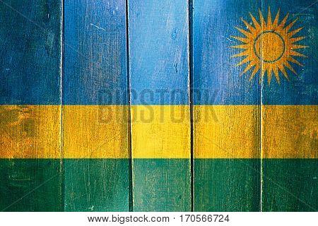 Vintage Rwanda  flag on grunge wooden panel
