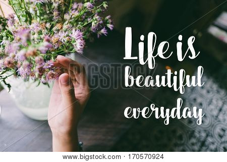 Life quote. Motivation quote on soft background. The hand touching purple flowers. Life is beautiful everyday.