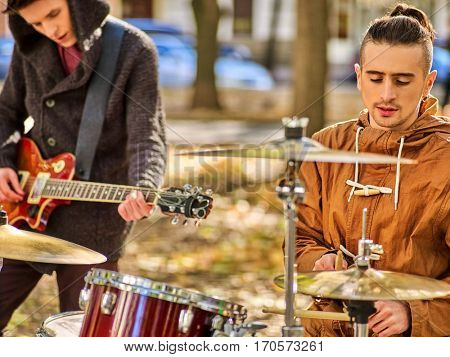 Festival music band. Cropped shot of male musicians playing on percussion instruments in city park . Drums with sticks and guitar closeup.