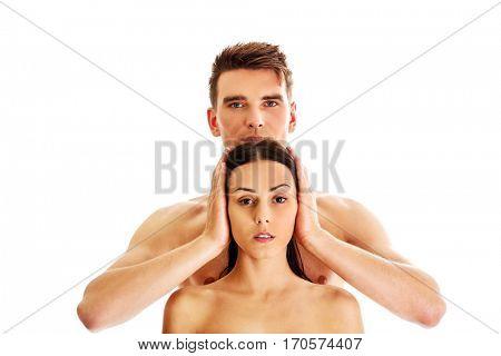 Man covering women's ears