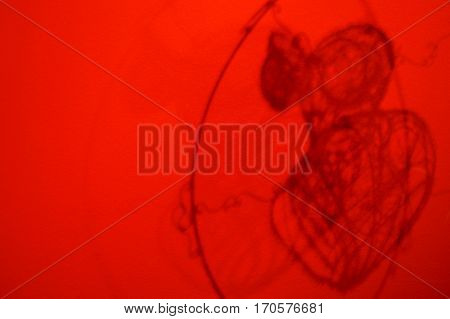 The abstract shadow of an erotic corset on a red wall.