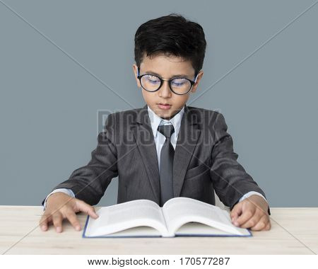 A Caucasian Boy With Glasses Reading Book Background Studio Portrait