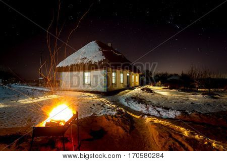 hot barbecue fire on old house background with thatch roof in winter night