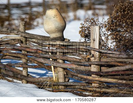 clay jug on wooden fence in winter day
