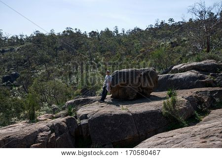 A man leaning on a large rock at John Forrest National park Western Australia