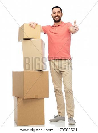 delivery, moving, people and logistics concept - happy man with pile of cardboard boxes showing thumbs up