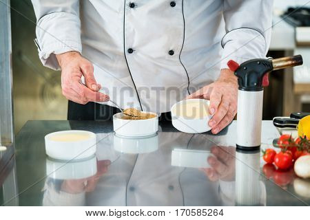 Chef or Patissier preparing a creme brulee putting sugar on top