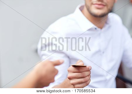 people, payment and finance concept - close up of man giving credit card to waiter