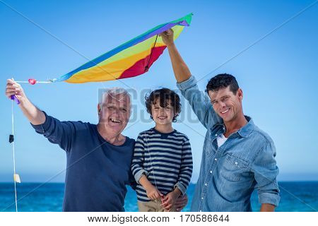 Happy multi generation family playing with a kite on the beach