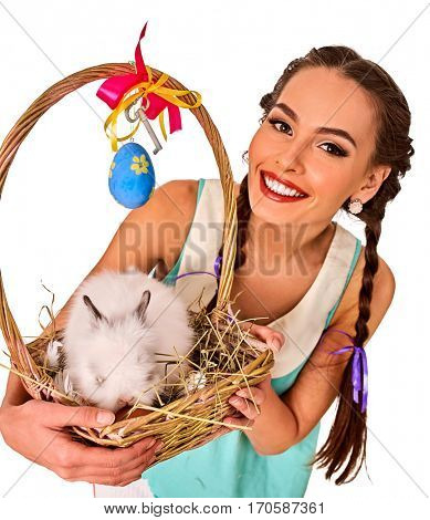Easter girl holding bunny and decoration eggs. Holiday style holding and rabbits in basket with flowers. White rabbit and background.