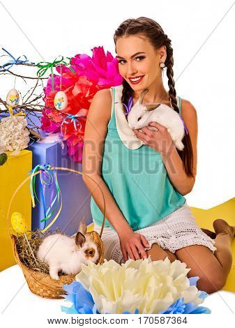 Easter bunny in girl's hands. Decoration egg holding by woman. Holiday style holding and group of rabbits in basket with flowers. Isolated. Young woman with present box at home. White background.