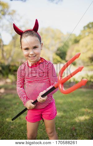 Little girl standing and dressing up as devil in the park