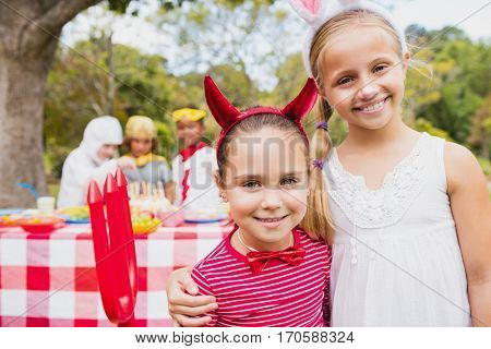 Smiling girls wearing costume during a birthday party in the park