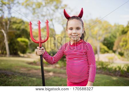 Little girl pretending to be a devil in the park