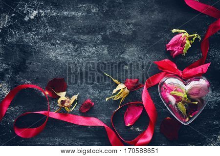 Valentine's Day composition with dried roses ribbon transparent heart box on black old metal surface