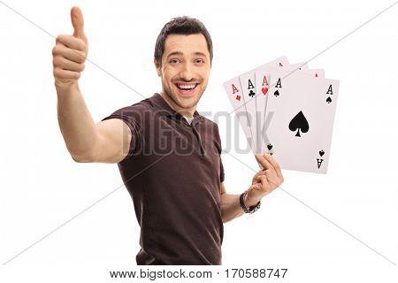Joyful guy making a thumb up sign and holding four aces isolated on white background