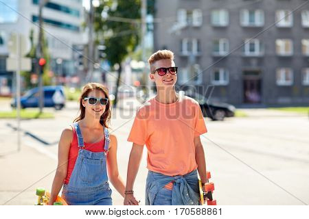 summer holidays, extreme sport and people concept - happy teenage couple with short modern cruiser skateboards walking along city street