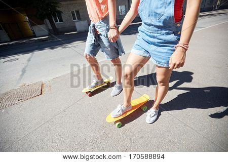 summer, relations, extreme sport and people concept - happy teenage couple riding short modern cruiser skateboards on city street