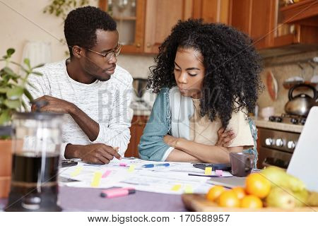 Young African Couple Quarreling Because Of Many Debts, Sitting At Kitchen Table With Documents, Calc