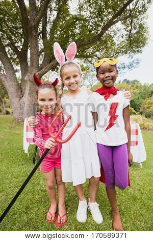 Three girls wearing costume posing for the camera in the park