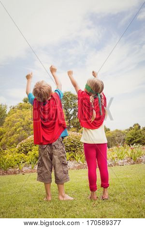Two children pretending to be superhero in the park