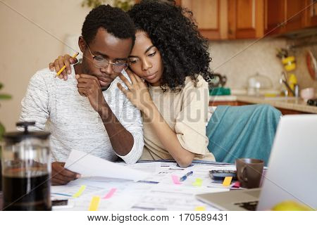 Family, Finances And Debts. Young African Couple Undergoing Financial Difficulties, Sitting At Kitch