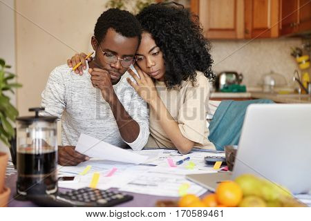 Young African Family Undergoing Financial Crisis. Beautiful Woman Embracing Her Husband While Readin