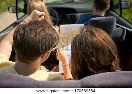 leisure, road trip, travel and people concept - happy friends with map driving in convertible car along country