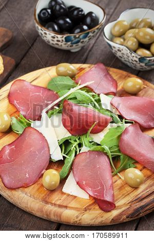 Charcuterie board with italian bresaola cured beef, cheese and rocket salad