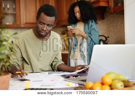 Busy Serious African Male Using Cell Phone While Calculating Family Expenses And Doing Paperwork, Si