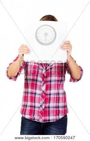 Woman covering her face with weight scale