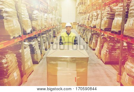 wholesale, logistic, loading, shipment and people concept - smiling man with loader carrying cargo at warehouse