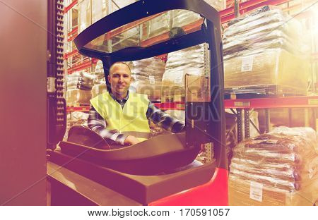 wholesale, logistic, loading, shipment and people concept - smiling man or loader operating forklift loader at warehouse