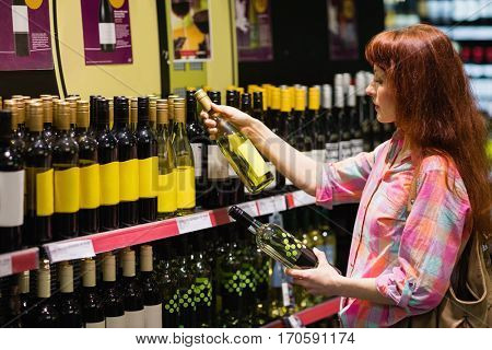 Consumer hesitating between two bottles of wine in supermarket