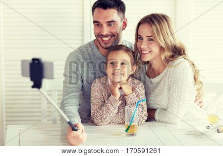 family, parenthood, technology and people concept - happy mother, father and little girl having dinner and taking picture by smartphone selfie stick at restaurant
