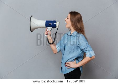 Side view of Woman in shirt screaming in megaphone and holding arm at hip. Isolated gray background