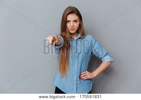Woman in shirt pointing at camera with arm at hip. Isolated gray background
