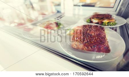 fast food, junk-food and unhealthy eating concept - close up of sandwich or burger in showcase of cafe or grocery store