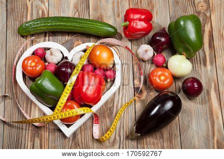 Sport and diet. Vegetables and centimeter. Peppers, tomatoes, garlic, onions, boklazhan, cucumber and radishes in the heart on rustic background